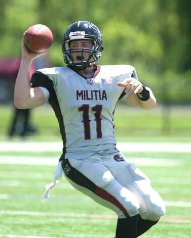 Militia quarterback Kevin Oberg scrambles before completing a six yard touchdown pass during an NEFL preseason game against the New York Red Rebels Saturday at Rogers Park. Photo: Barry Horn / The News-Times Freelance