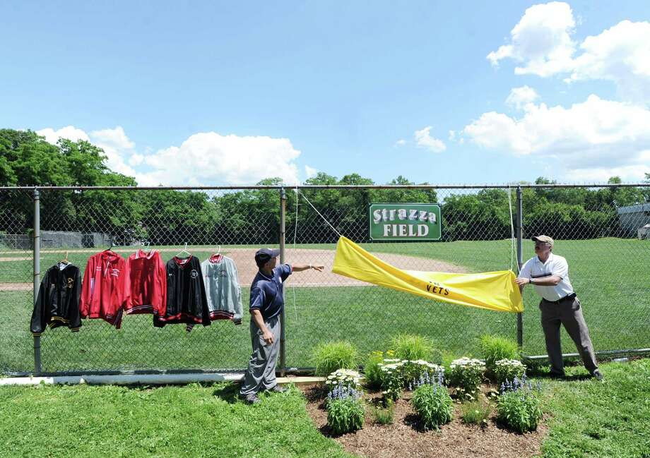 At left, state Rep. Alfred Camillo, R-151st District, and George Zaccagnini, unveil the Strazza Field sign during the dedication of the Salvatore J. Strazza Sr. Memorial baseball field in Byram, Saturday afternoon, June 23, 2012. Longtime Byram resident Sal Strazza and fellow baseball enthusiast George Zaccagnini revived a financially struggling Babe Ruth baseball league in the 1970s and were instrumental in its growth through the decades. Strazza died in 2001 at age 60 after a bout with cancer. Photo: Bob Luckey / Greenwich Time