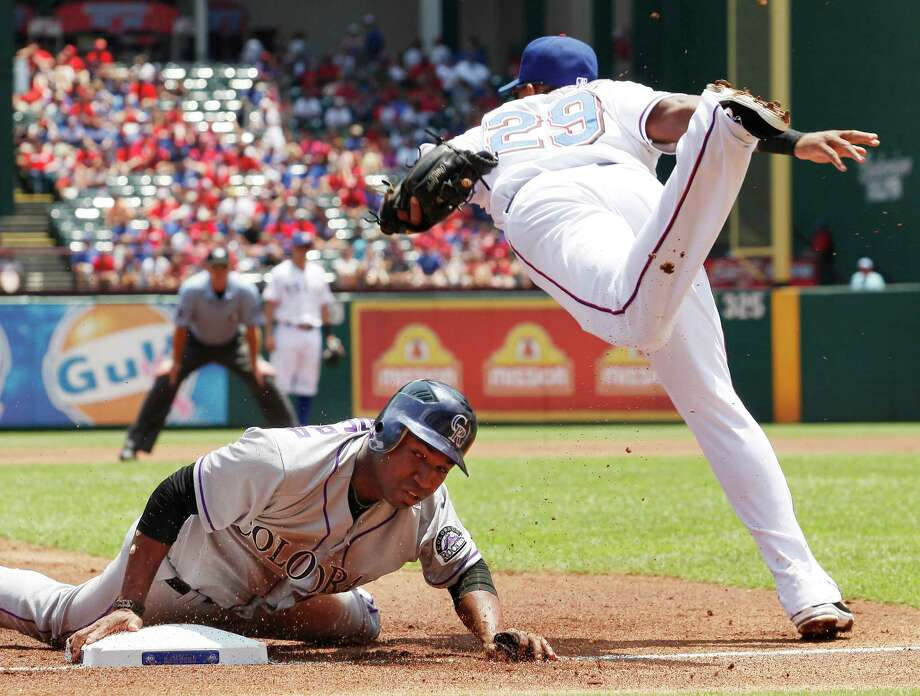 Texas Rangers third baseman Adrian Beltre, right, jumps after missing the tag as Colorado Rockies' Jonathan Herrera safely steals third base during the first inning of an interleague baseball game on Saturday, June 23, 2012, in Arlington, Texas. Photo: AP