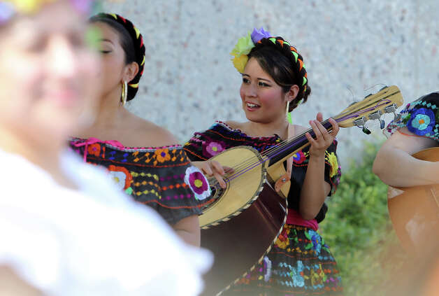 "Amanda Lozano (center) plays the ""guitarron"" with Mariachi Flor de Jalisco as part of the day's musical entertainment as the Texas Historical Commission, Friends of Casa Navarro and the Cortez Family unveil a mural created by artist Jesse Trevino and his wife Elizabeth Rodriguez at the Casa Navarro State Historic Site on Saturday, June 23, 2012. Photo: Kin Man Hui, Express-News / ©2012 San Antonio Express-News"