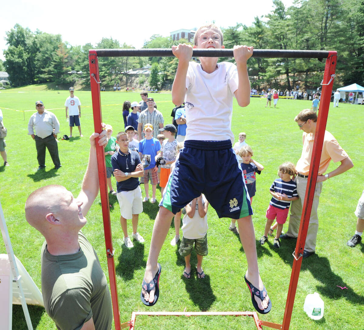 Joseph McCurdy, 10, of Greenwich does chin-ups while being spotted by U.S. Marine Kevin Dickson, left, during the Salute to Veterans ceremony at Havemeyer Field in Greenwich, Saturday afternoon, June 23, 2012.