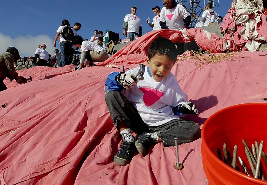 "Sarek Mallareddy, 4, hammers a spike during the annual event of the installation of the Pink Triangle by volunteers with ""Friends of the Pink Triangle"", on Saturday June 23, 2012, now  covers the Eastern hillside of Twin Peaks, in San Francisco, Calif. Photo: Michael Macor, The Chronicle"