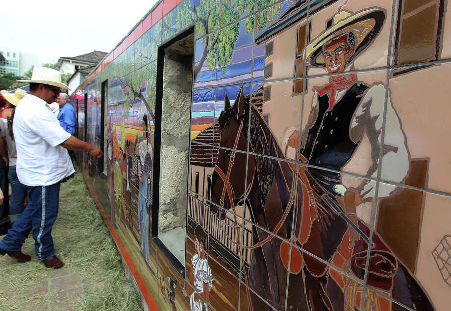 Guests admire the mural created by artists Jesse Trevino and his wife Elizabeth Rodriguez at the Casa Navarro State Historic Site after the unveiling ceremony on Saturday, June 23, 2012. Photo: Kin Man Hui, San Antonio Express-News / ©2012 San Antonio Express-News