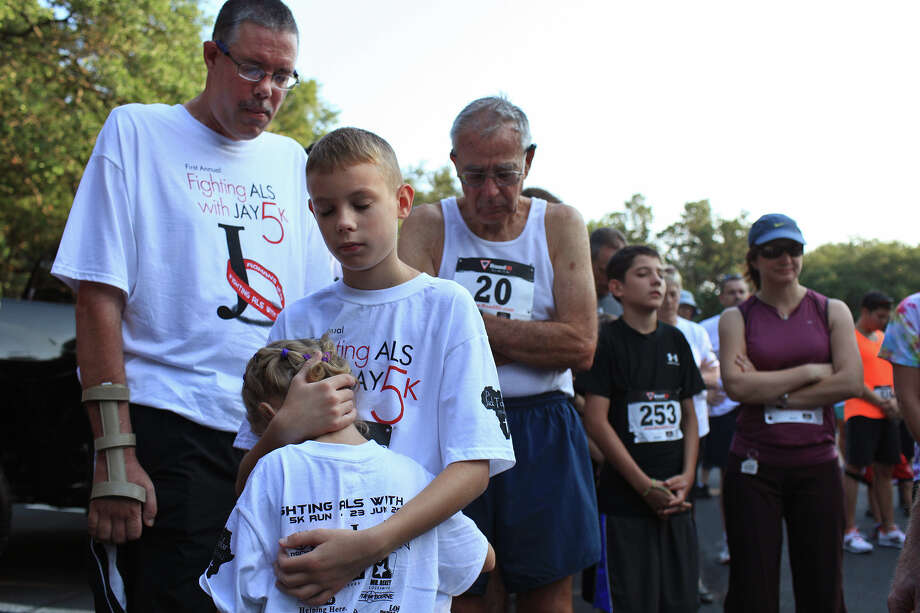 Jay Tolar, who has ALS, left, stands in prayer with his children, Jake Tolar, 11, and Julie Tolar, 4, and Al Bierling, center, of Denver, CO, who was Jay's running coach and math coach in Nigeria, before the First Annual Fighting ALS with Jay 5k in San Antonio on Saturday, June 23, 2012. The race was created and put on by Tolar's sister, Laura Birdy, and her husband, David Birdy, of San Antonio. Photo: Lisa Krantz, San Antonio Express-News / 2012 San Antonio Express-News