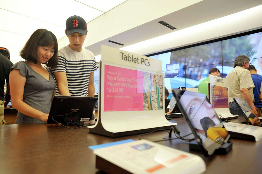 Brookfield residents Hyunji Kim, left, and her husband, Injik Lee, look at tablets during the opening day of the Microsoft store at the Danbury Fair mall on Saturday, June 23, 2012. Photo: Jason Rearick / The News-Times