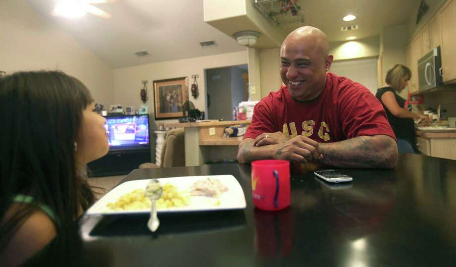 Michael Rivera jokes with his daughter Madison, 7, during dinner Monday, June 4, 2012, in their home. Rivera has been incarcerated twice over the past 18 years and has struggled with employment in the past. He was released in 2011 and was employed two weeks after at The Original Mexican Restaurant as a busboy for about eight months. Rivera has been working with a demolition and remodeling company for three weeks now and contributes his success of finding employment to friends. Photo: Julysa Sosa, SAN ANTONIO EXPRESS-NEWS / SAN ANTONIO EXPRESS-NEWS