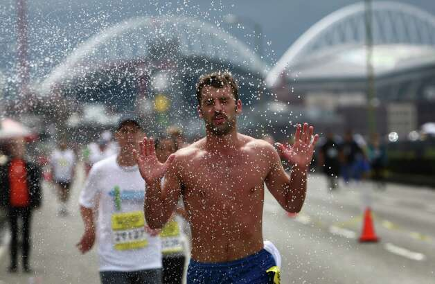 A competitor runs through a sprinkler set up on the Alaskan Way Viaduct. Photo: JOSHUA TRUJILLO / SEATTLEPI.COM