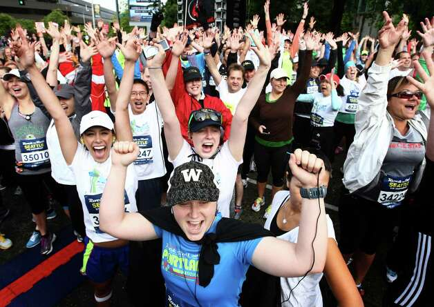 Runners throw up their arms at the start. Photo: JOSHUA TRUJILLO / SEATTLEPI.COM