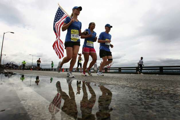 Lisa Hallett, left, carries a flag for her husband, Capt. John Hallett, who was killed in Afghanistan in 2009. She was running with the Wear Blue, Run to Remember group, including Rita White, center, and  Denny Bernardy. Photo: JOSHUA TRUJILLO / SEATTLEPI.COM