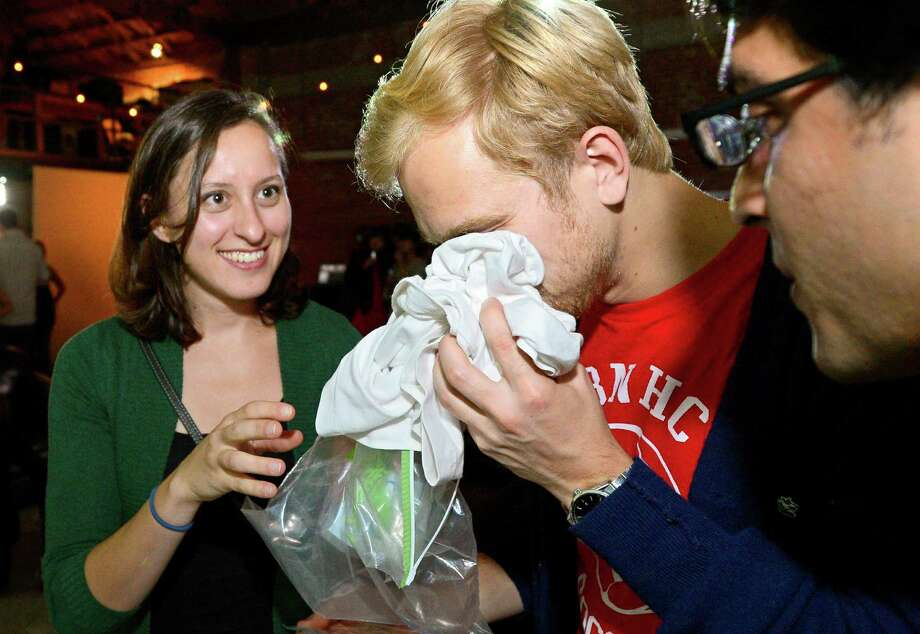 Konstantin Bakhurin, center, smells a shirt as Martina Desalvo, left, and Neelroop Parikfhak look on during a pheromone party, Friday, June 15, 2012, in Los Angeles. The get-togethers, which have been held in New York and Los Angeles and are planned for other cities, require guests to submit a slept-in T-shirt that will be sniffed by other participants. Then you can pick your partner based on scent. (AP Photo/Mark J. Terrill) Photo: Mark J. Terrill / AP