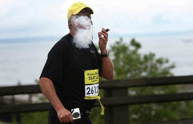 Runner Chris Ackerman enjoys a cigar as he runs the final stretch. Ackerman said he has run about 30 marathons and figured he'd celebrate as he neared the finish line. Photo: JOSHUA TRUJILLO / SEATTLEPI.COM