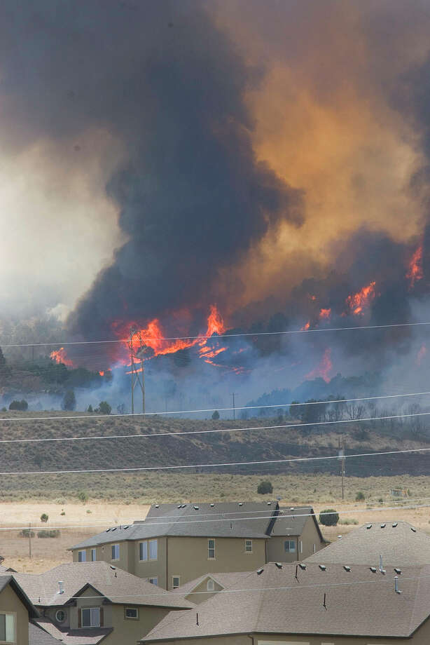 A wildfire west of Utah Lake sends flames shooting into the sky on Friday. Residents of at least 2,300 homes in northern Utah were forced to evacuate. by target shooters. (AP Photo/Paul Fraughton, Salt Lake Tribune) Photo: Paul Fraughton / Salt Lake Tribune