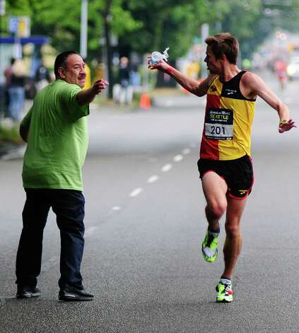 Half marathon winner Robert Scribner loses his grasp on a cup as he passes a water station. Photo: LINDSEY WASSON / SEATTLEPI.COM
