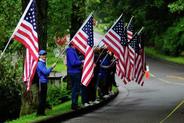 People hold flags to honor military members on Lake Washington Boulevard South. Photo: LINDSEY WASSON / SEATTLEPI.COM