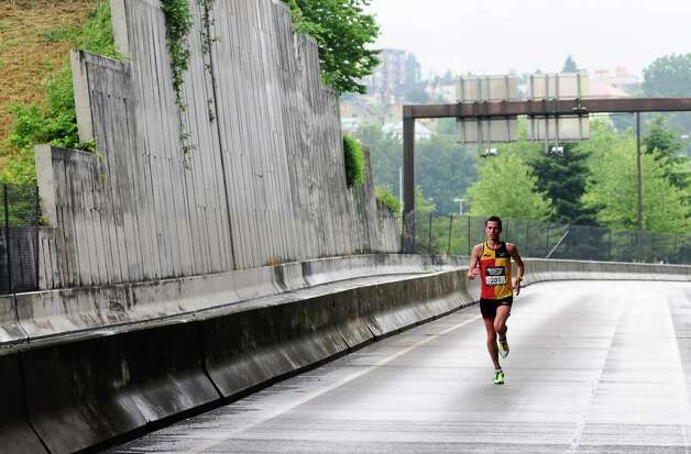 Half-marathon winner Robert Scribner, 26, of Michigan, runs on I-90 with a substantial lead. Photo: LINDSEY WASSON / SEATTLEPI.COM