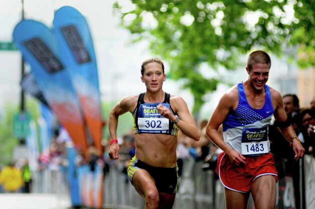 Two half-marathon runners approach the finish line. Photo: LINDSEY WASSON / SEATTLEPI.COM