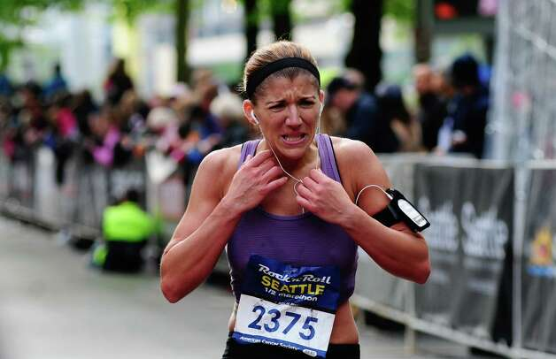 A runner grimaces as she makes her way past the half-marathon finish line. Photo: LINDSEY WASSON / SEATTLEPI.COM