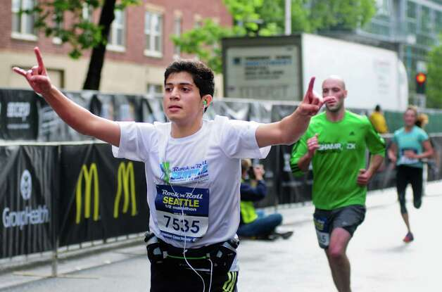 "A runner throws up some ""rock hands"" as he finishes the half-marathon. Photo: LINDSEY WASSON / SEATTLEPI.COM"