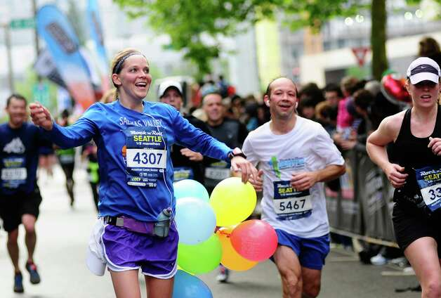 A half-marathon runner dances as she nears the finish with several balloons tied to her waist. Photo: LINDSEY WASSON / SEATTLEPI.COM