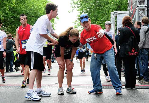 A medical volunteer shows a queasy runner to a trash can at the finish line. Photo: LINDSEY WASSON / SEATTLEPI.COM