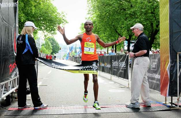 Teshome Kokebe, 30, of Lynnwood, throws out his arms as he wins the marathon. Photo: LINDSEY WASSON / SEATTLEPI.COM