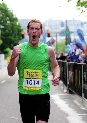 The third-place marathon runner shouts and pumps his fist as he runs towards the finish Photo: LINDSEY WASSON / SEATTLEPI.COM
