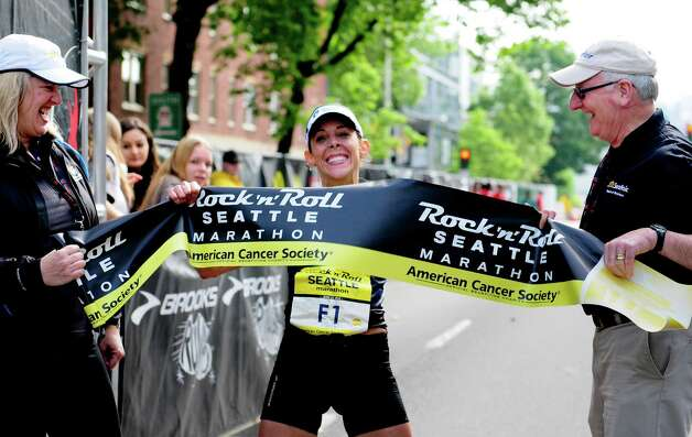 Sheila Croft of Redmond smiles and grabs the finishing banner as she becomes the first woman to finish.  Croft's finishing time was 2 hours and 41 minutes. Photo: LINDSEY WASSON / SEATTLEPI.COM