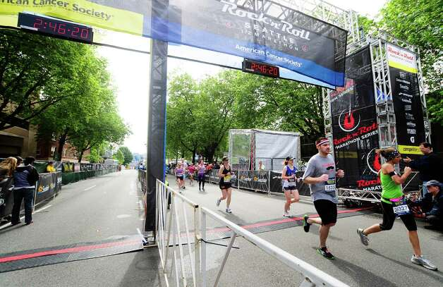 Half-marathon runners cross the finish line. Photo: LINDSEY WASSON / SEATTLEPI.COM