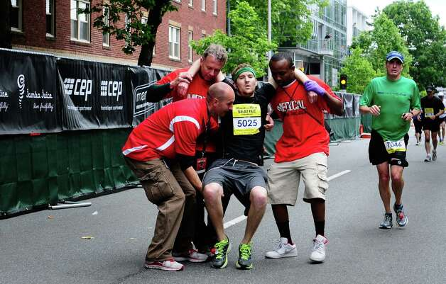 A collapsed runner is helped to the marathon finish line by medical volunteers. Photo: LINDSEY WASSON / SEATTLEPI.COM