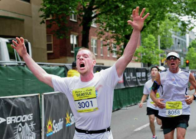 A runner throws up his arms and shouts as he finishes. Photo: LINDSEY WASSON / SEATTLEPI.COM