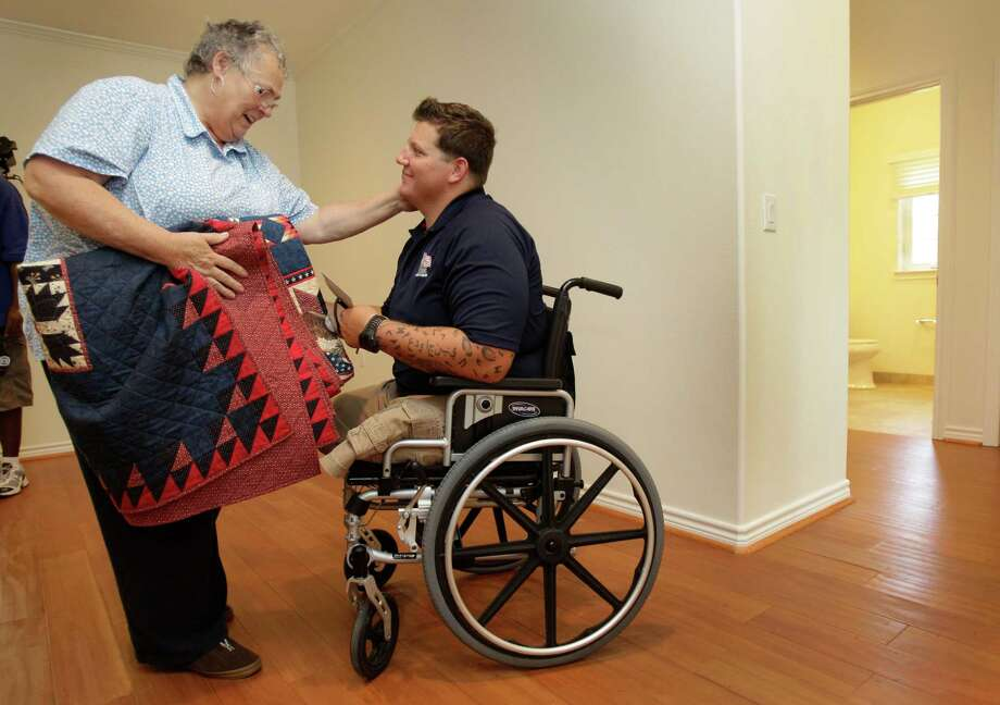 Donna Mitchell of San Antonio gives a patriotic themed quilt she made to Marine Cpl. Daniel Peterson after a Homes for Our Troops key ceremony at his new home Saturday, June 23, 2012, in Tomball.  Homes for Our Troops gives specially adapted home to severely injured veterans. Photo: Melissa Phillip, Houston Chronicle / © 2012 Houston Chronicle