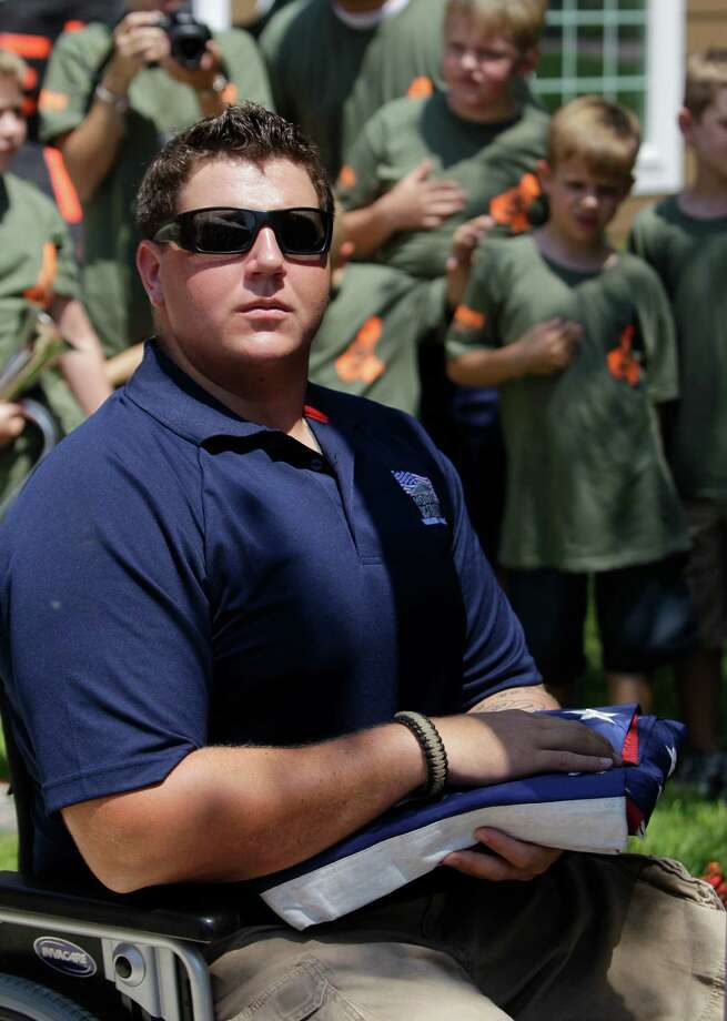 Marine Cpl. Daniel Peterson prepares to raise the U.S. flag during the Homes for Our Troops key ceremony. Photo: Melissa Phillip, Houston Chronicle / © 2012 Houston Chronicle