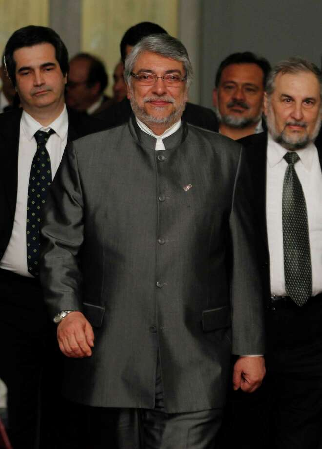 Paraguay's President Fernando Lugo leaves his office on his way to address the nation at the presidential palace in Asuncion, Paraguay, Friday, June 22, 2012.  Paraguay's Senate has voted to remove Lugo from office in an impeachment trial, and his vice president was promptly sworn in as president. Lugo said he would leave office even though he considered his ouster by Friday's Senate vote a blow to democracy. (AP Photo/Jorge Saenz) Photo: Jorge Saenz