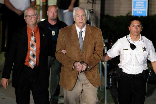 Former Penn State University assistant football coach Jerry Sandusky, center, leaves the Centre County Courthouse in custody with Centre County Sheriff Denny Nau, left, after being found guilty of multiple charges of child sexual abuse in Bellefonte, Pa., Friday, June 22, 2012. Sandusky was convicted of sexually assaulting 10 boys over 15 years, accusations that had sent shock waves through the college campus known as Happy Valley and led to the firing of Penn State's beloved Hall of Fame coach, Joe Paterno. (AP Photo/Gene J. Puskar) Photo: Gene J. Puskar