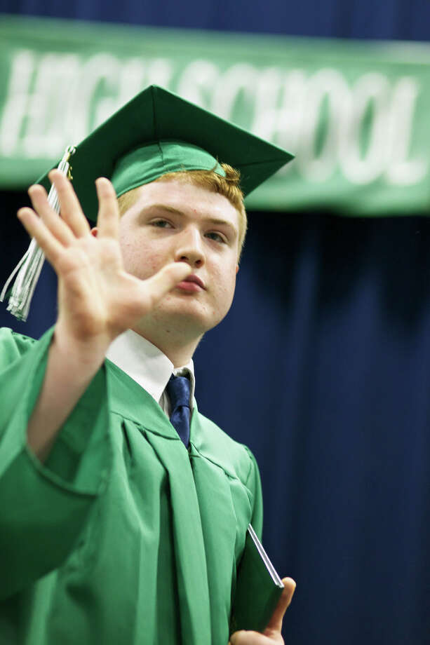 After receiving his diploma,  Timothy Heydenburg waves in acknowledgment as his many friends and family cheer his name during the New Milford High School Class of 2012 exercises which took place on Saturday, June 23, 2012 , at The O'Neill Center at WCSU in Danbury, CT. Photo: News Times Contributed