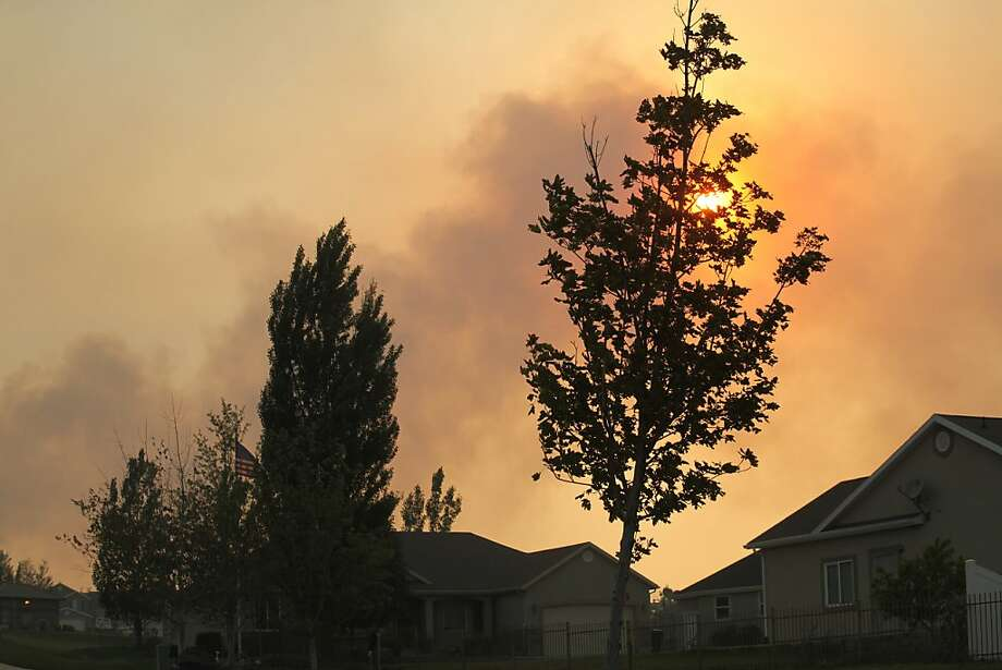 Smoke fills the sky above Saratoga Springs, Utah,  Friday, June 22, 2012, where homes have been evacuated because of a raging wildfire. Thousands have been forced to evacuate as high winds and tinder-dry conditions hampered fire-fighting efforts.(AP Photo/Lynn DeBruin) Photo: Lynn DeBruin, Associated Press
