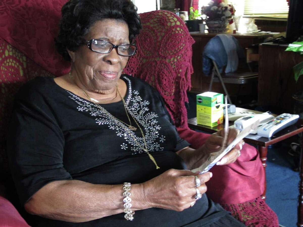 In a Wednesday, June 20, 2012 photo, Dearline Sims holds news clippings in her Dallas home, about her nephew, Larry Sims, who was convicted of aggravated sexual assault and spent 24 years in prison before new DNA evidence led to his being freed. But Sims, 62, died in June without ever being fully exonerated, something that his family and friends say troubled him until his death.