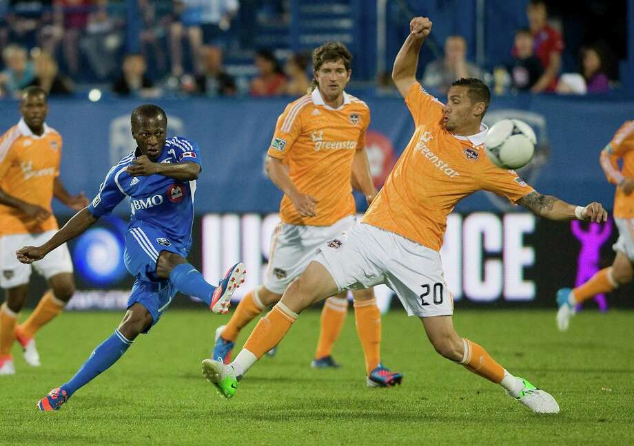 Sanna Nyassi, left, strikes the ball past Houston Dynamo's Geoff Cameron during the second half. Photo: Graham Hughes, Associated Press / The Canadian Press