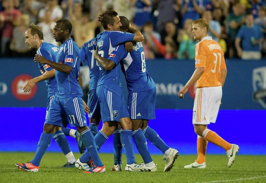 Patrice Bernier is congratulated by after scoring against the Dynamo as Andre Hainault (31) walks past during the second half.  Photo: Graham Hughes, Associated Press / The Canadian Press