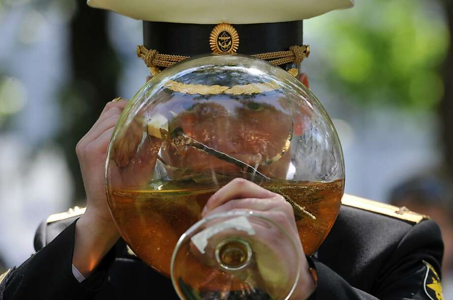 He has trouble holding his liquor:A newly promoted Russian  naval lieutenant chugs wine from a fishbowl-sized goblet during  graduation from Navy Institute in St. Petersburg. His personal naval  officers' dirk serves as a swizzle stick Photo: Olga Maltseva, AFP/Getty Images
