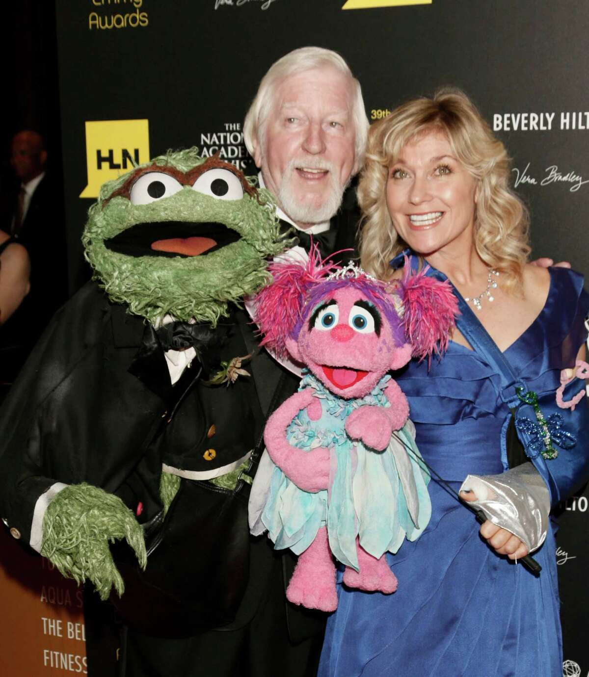 Caroll Spinney, left, and Leslie Carrara Rudolph pose with puppets Oscar the Grouch, left, and Abby Cadabby.