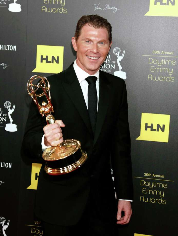 "Bobby Flay poses backstage with the culinary program award for ""Barbecue Addiction."" Photo: TODD WILLIAMSON/INVISION/AP"