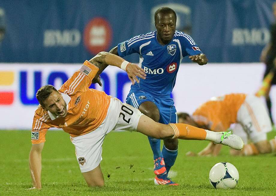 The Impact's Sanna Nyassi, right, and the Dynamo's Geoff Cameron battle for possession during the second half of Montreal's home victory. Photo: Graham Hughes / The Canadian Press