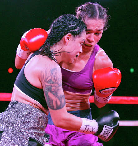 Christina Ruiz (left) and Nohime Dennisson exchange punches during the first round of their boxing match Saturday June 23, 2012 at Maverick Plaza in La Villita. The fight was a majority draw. Photo: Edward A. Ornelas, Express-News / © 2012 San Antonio Express-News