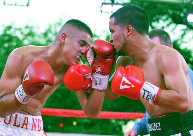 Rolando Campos (left) and Henry Hernandez exchange punches during the second round of their boxing match Saturday June 23, 2012 at Maverick Plaza in La Villita. Campos went on to win by unanimous decision. Photo: Edward A. Ornelas, Express-News / © 2012 San Antonio Express-News