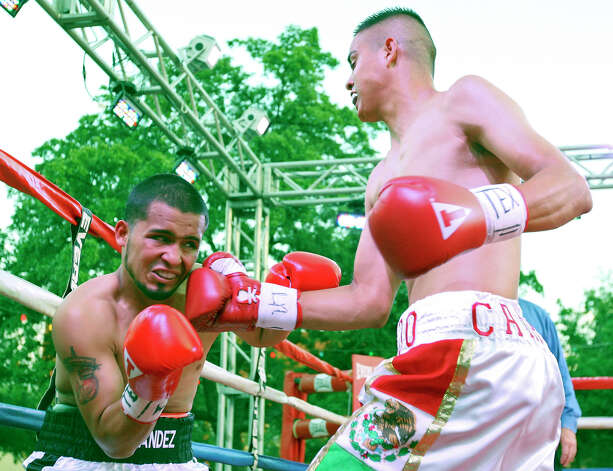 Henry Hernandez (left) is hit by Rolando Campos during the first round of their boxing match Saturday June 23, 2012 at Maverick Plaza in La Villita. Campos went on to win by unanimous decision. Photo: Edward A. Ornelas, Express-News / © 2012 San Antonio Express-News