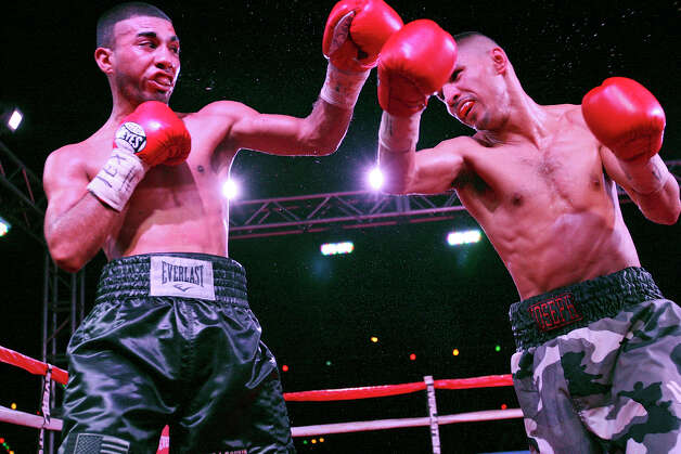 Joel Garcia (left) and Joseph Rios exchange punches during the sixth round of their boxing match Saturday June 23, 2012 at Maverick Plaza in La Villita. Rios won by a majority decision. Photo: Edward A. Ornelas, Express-News / © 2012 San Antonio Express-News
