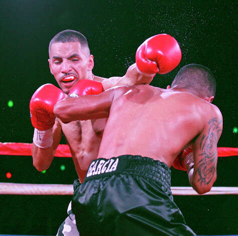 Joseph Rios (left) and Joel Garcia exchange punches during the fourth round of their boxing match Saturday June 23, 2012 at Maverick Plaza in La Villita. Rios won by a majority decision. Photo: Edward A. Ornelas, Express-News / © 2012 San Antonio Express-News