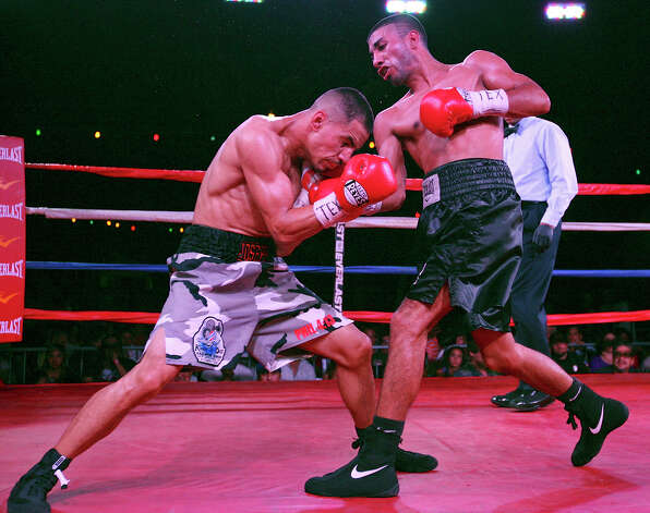 Joseph Rios (left) and Joel Garcia exchange punches during the second round of their boxing match Saturday June 23, 2012 at Maverick Plaza in La Villita. Rios won by a majority decision. Photo: Edward A. Ornelas, Express-News / © 2012 San Antonio Express-News