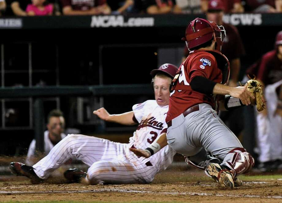 South Carolina's Tanner English (3) scores at home plate against Arkansas catcher Jake Wise on a single by Joey Pankake, in the fifth inning of an NCAA College World Series baseball elimination game in Omaha, Neb., Friday, June 22, 2012. The winner advances to play Arizona in the championship series. (AP Photo/Ted Kirk) Photo: Ted Kirk